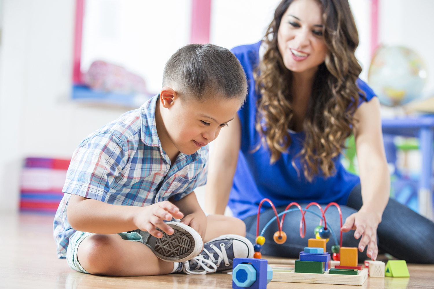 Sweet little Hispanic boy with Down Syndrome sits cross legged on the floor of a daycare center and reaches for toys. His female Hispanic young adult teacher sits on the floor with him and reaches for a different toy.