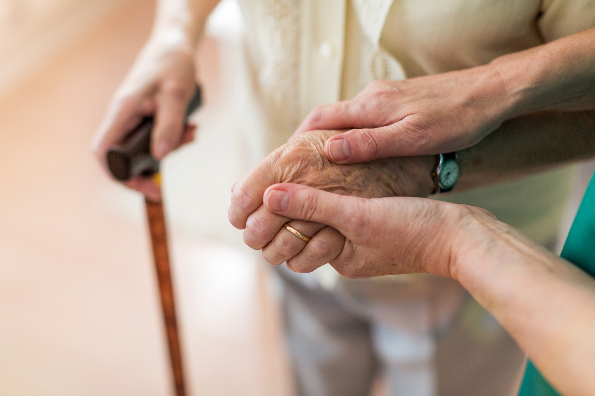 Nurse consoling her elderly patient by holding her hands